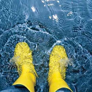 person in rubber boots standing in a flooded basement in Columbus Ohio
