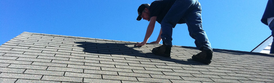 benchmark employee inspecting a roof's shingles